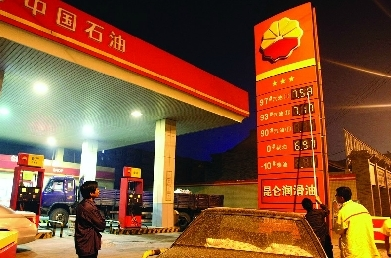 10月9日凌晨,西安环城北路西段一家加油站,工作人员正在变更油价数据,一位货车司机等着油价下调后加油。