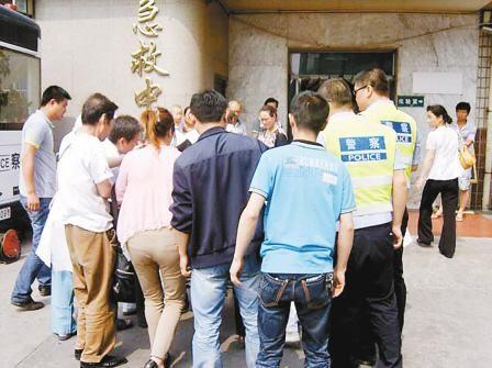 图为民警群众集体护送笑笑抵达医院。(图片来源:西安日报)