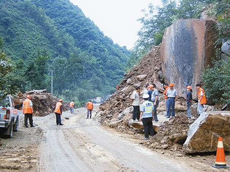 昨日,抢险人员在中断的108国道宁强段打通便道,但要全部畅通需爆破阻路巨石。