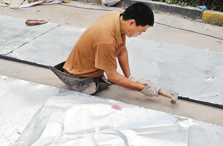 昨日,刘满义和工友给一家楼盘安装广告牌,他负责用榔头把铁皮钉在框架上。