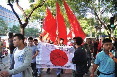 """昨天,群众在日本驻华大使馆附近打标语、喊口号,反对日本非法""""购买""""钓鱼岛。本报实习记者杨昊宇摄"""