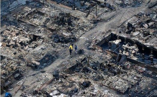 当地时间10月30日,美国纽约皇后区,人们站在被烧毁的房屋残骸中。
