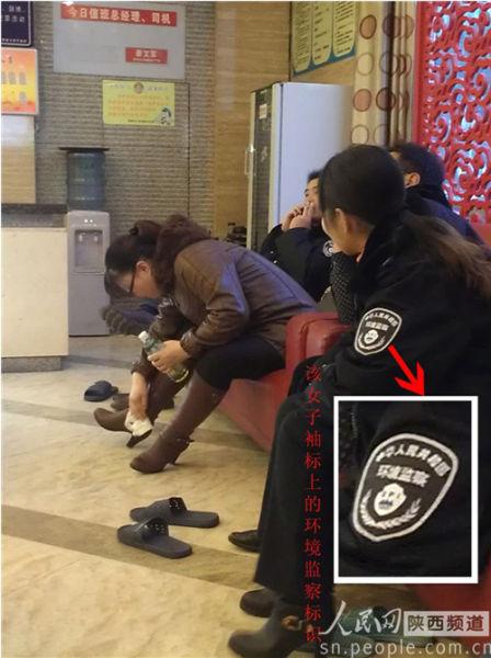 """洗浴完毕坐在沙发区休息的这位女子,袖标上赫然印着""""中华人民共和国环境监察"""",另一边穿制服的男子也在悠闲的抽着烟。"""