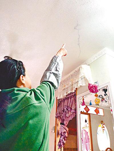 被腐尸水渗入屋内的女户主鲁女士指示天花上的渗漏位置。香港《文汇报》
