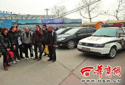 几名乐山人站在一辆四川牌照的警车前,他们担心被拦截送回四川 本报记者 李晖 摄
