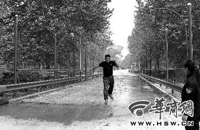 新增的模拟湿滑路面行驶,工作人员打伞调试设备,感受降雨