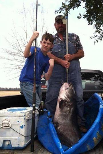 图为12岁的劳森及家人和巨型鲶鱼合影。