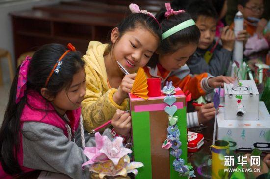 4月21日,合肥常胜小学的学生在用废旧物品制作手工作品。
