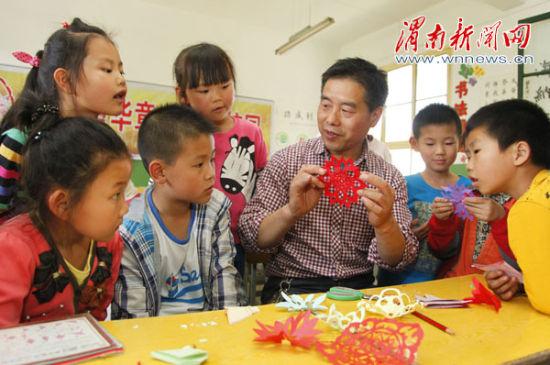 学生向 非遗 传承人学习剪纸技艺