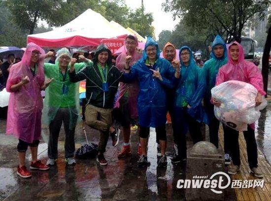 西安邮电大学团委学生干部穿着雨披在火车站迎接新生。