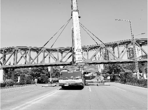 7月 15日,在经过数小时交通管制与紧张施工后,位于市区高新大道的人行过街天桥主桥梁部分顺利完成吊装。据悉,这座天桥是目前我市最大的人行过街天桥,预计 9月初投入使用。   当天上午,记者在高新大道看到,位于宝鸡文理学院东门口的马路南北两边桥墩已经完工,工作人员正在对建造好的主桥梁进行最后测量。 11时 30分,只听现场指挥员一声令下,启动吊装作业。在一台 450吨吊车的轰鸣声中, 120吨重的主桥梁从组装地徐徐升起。在指挥员的指挥下,经过不断提升、调整方向,吊车将主桥梁吊运到位,缓缓降落在固定支撑点